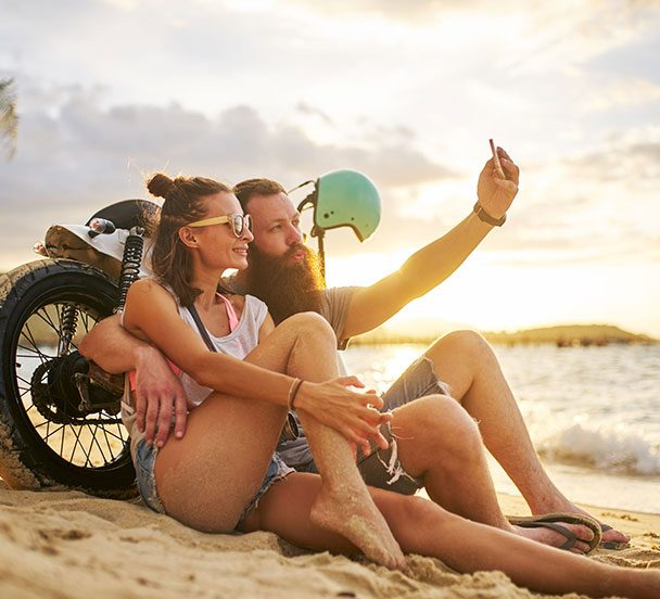 Couple in Thailand taking a selfie on the beach.