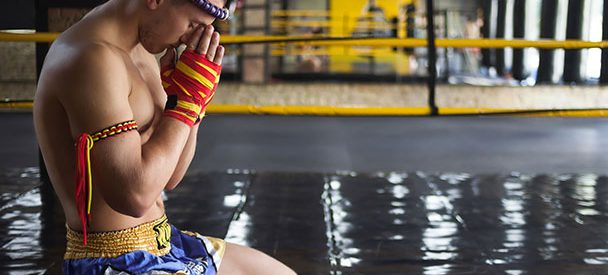 Muay Thai fighter kneeling to pray ringside.