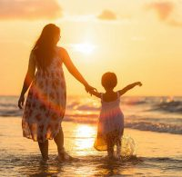 Mother and daughter on beach at sunset.