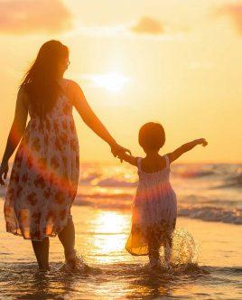 Mère et fille sur la plage avec coucher de soleil.