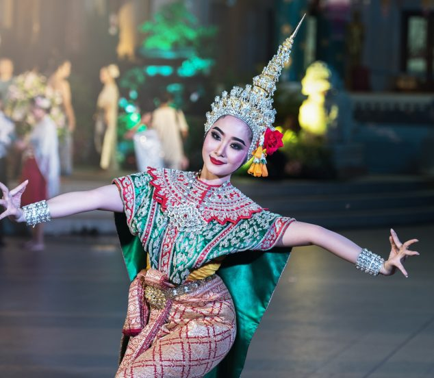 Woman in traditional Thai costume performing traditional Thai dance.