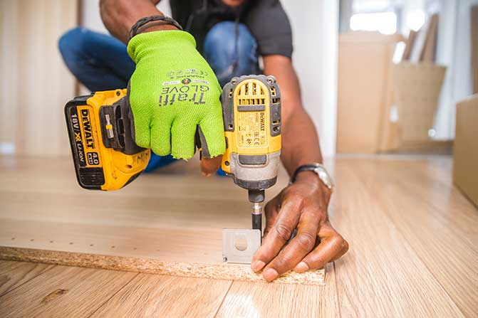 Worker using electric drill on construction site.