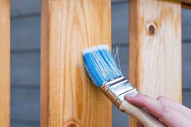 Paint brush on a wooden fence.